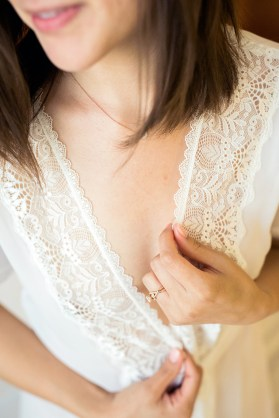 close up of hands on white lace robe