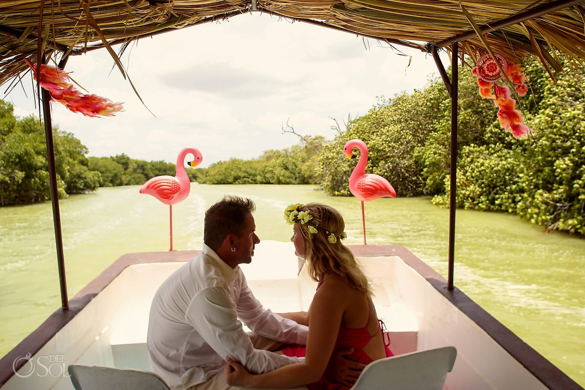 Bride and groom in a flamingo boat on the way to their custom ceremony