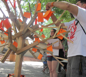 MEMORY TREE: Robert Duran hangs a note on the memory tree in the quad on Tuesday, April 30.