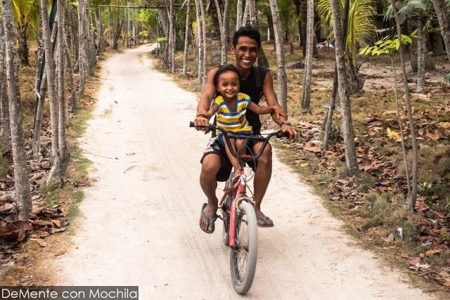 Padre e hija andando en bicicleta por una calle de Malapascua.