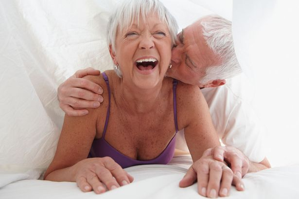Caucasian-couple-playing-under-sheet-in-bed
