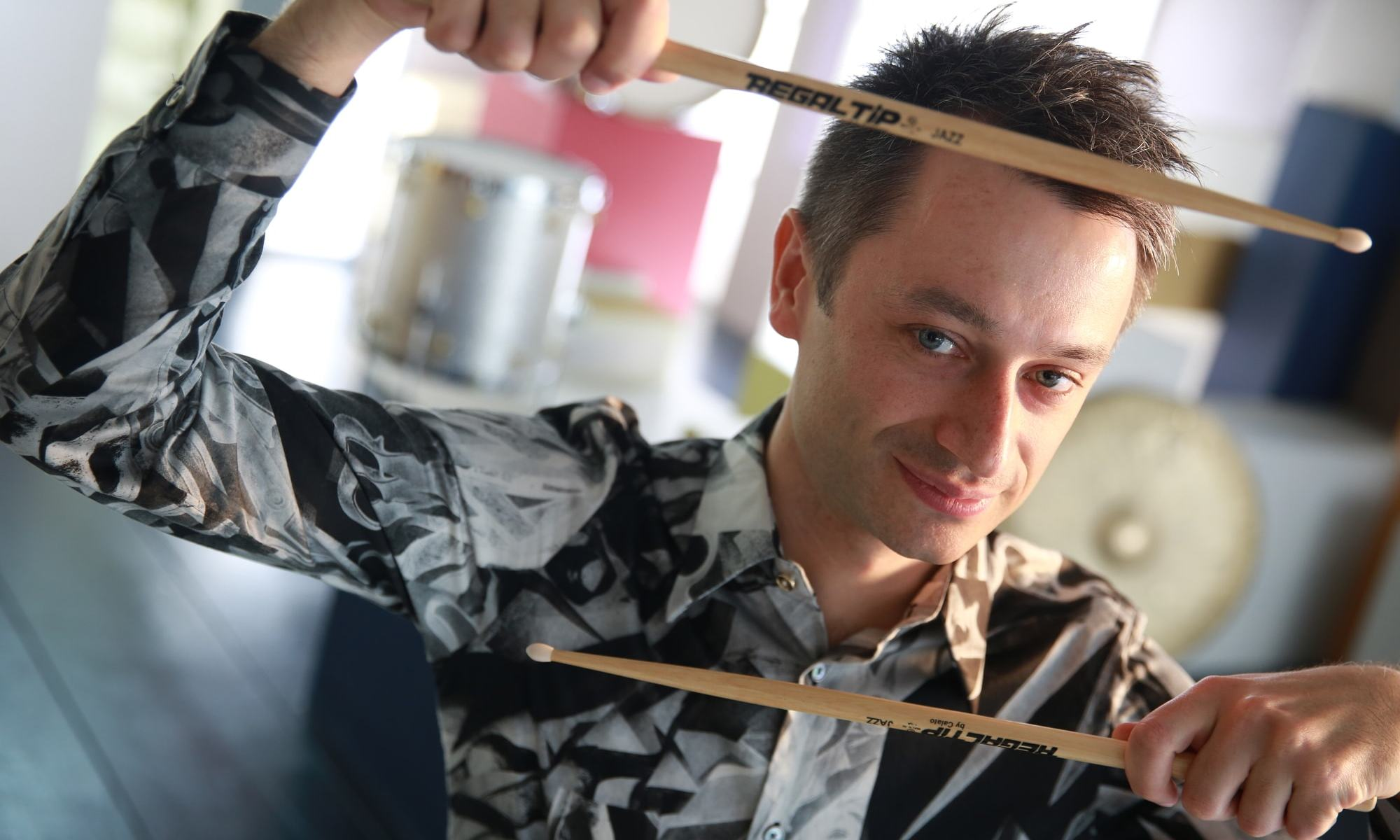 Dennis Frehse holding his regaltip drum sticks in a funny way in front of his face to create a frame for his face.
