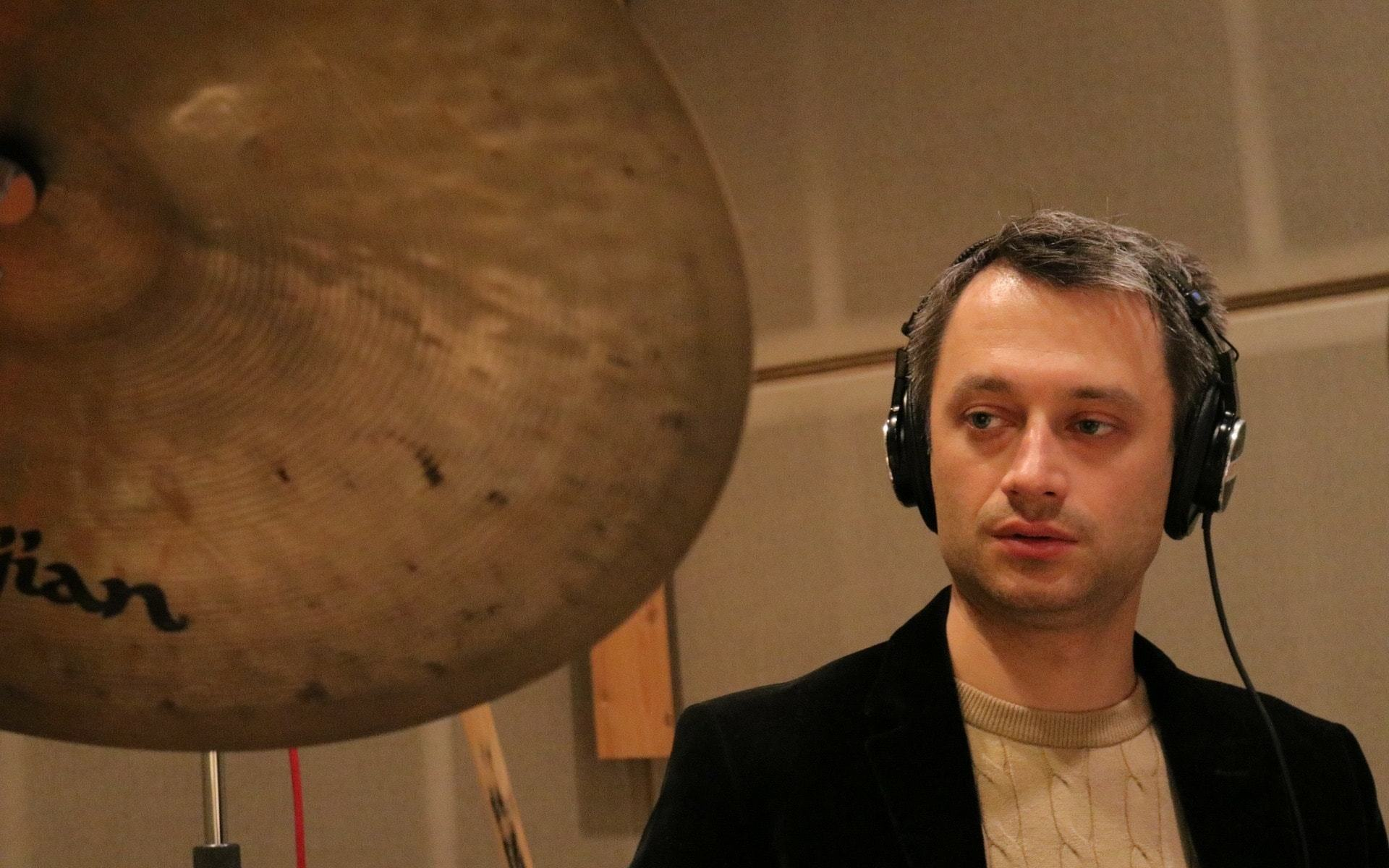 Dennis Frehse is recording drums in a studio session and is wearing Sony headphones.