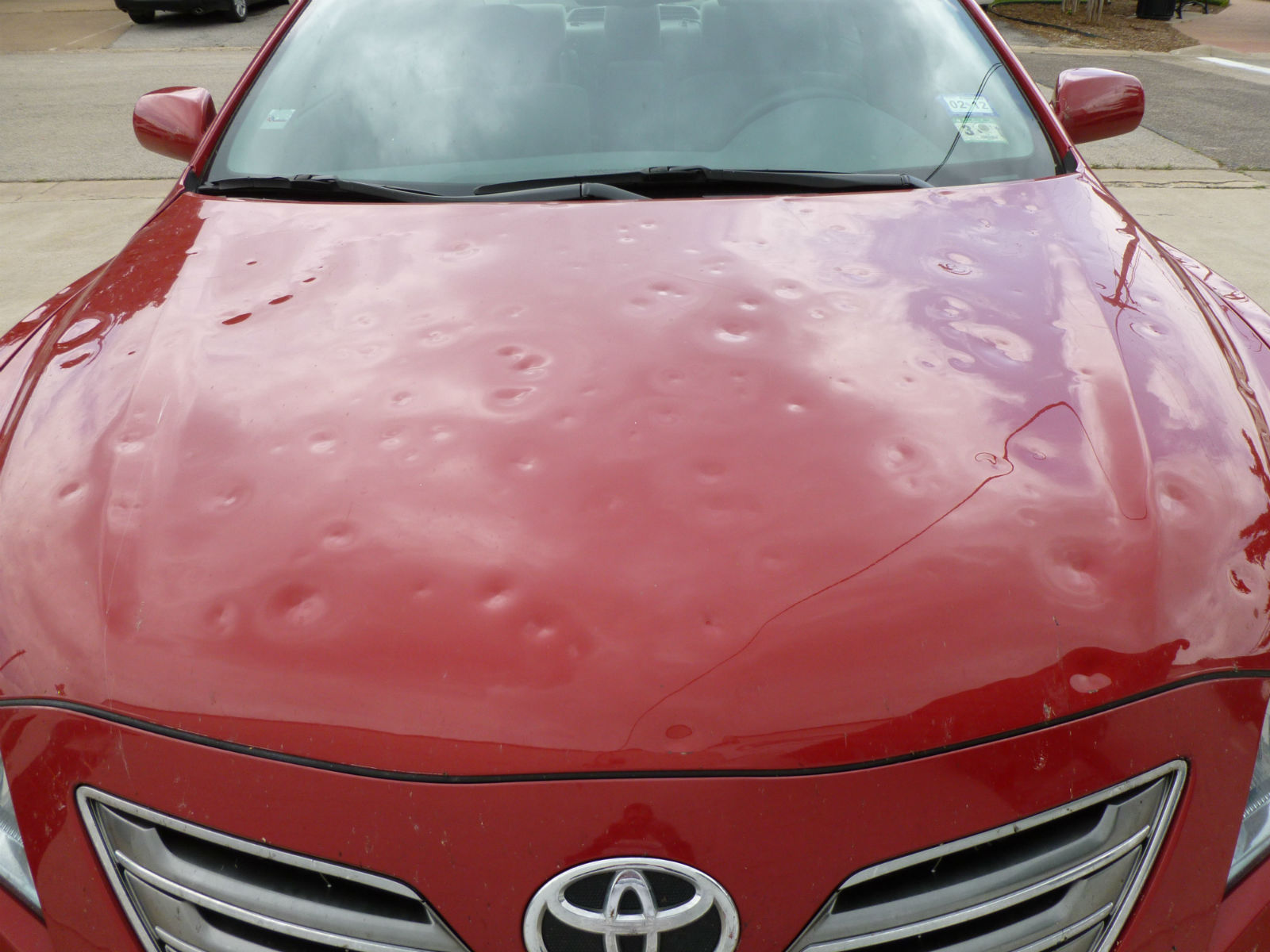 Toyota Camry Hood Pummeled By Baseball Sized Hail Dent