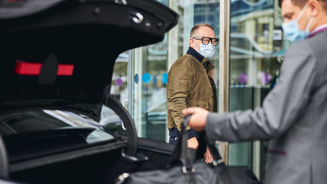 chauffeur with mask helping with luggage