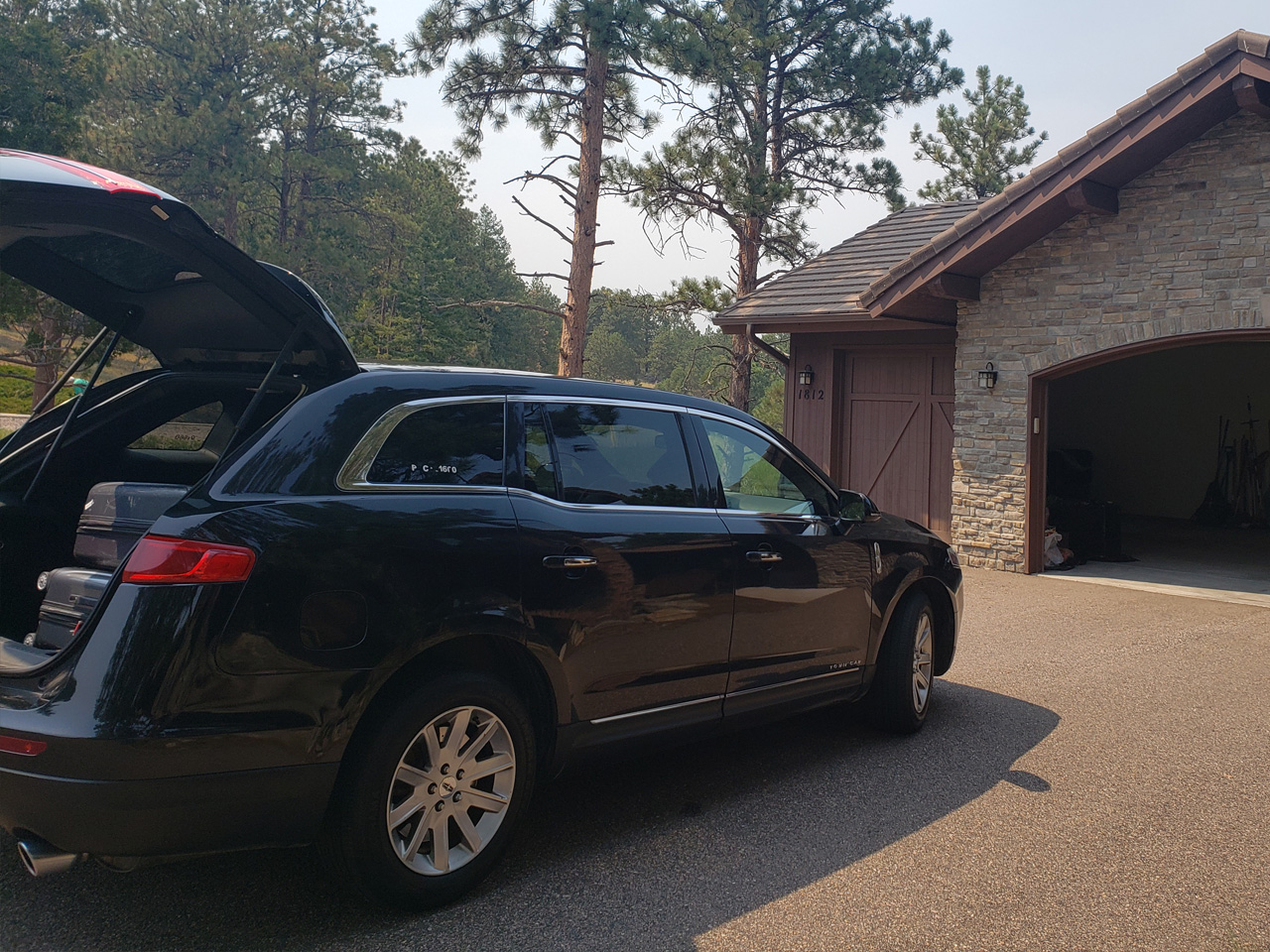 black luxury sedan waiting for a ride outside a home at Genesee Colorado