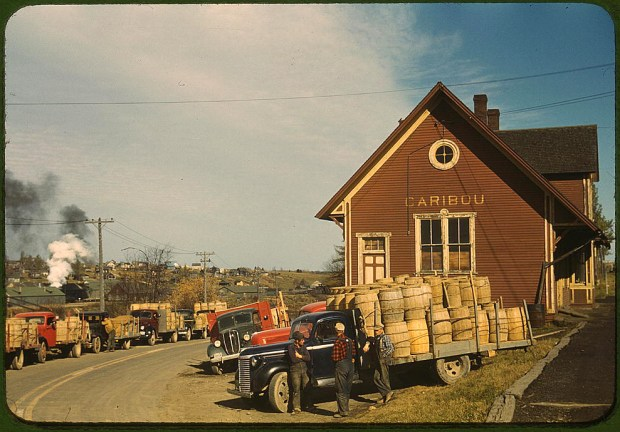 Trucks outside of a starch factory. Caribou, Aroostook County, Maine, October 1940. Reproduction from color slide. Prints and Photographs Division, Library of Congress