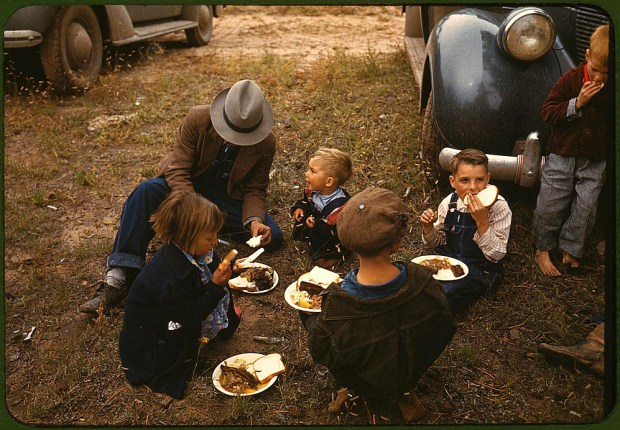Homesteader and his children eating barbecue at the New Mexico Fair. Pie Town, New Mexico, October 1940. Reproduction from color slide. Prints and Photographs Division, Library of Congress
