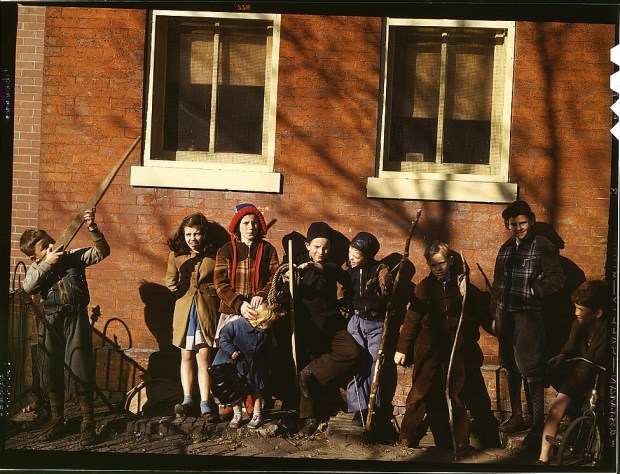 Children aiming sticks as guns, lined up against a brick building. Washington, D.C., between 1941 and 1942. Reproduction from color slide. Prints and Photographs Division, Library of Congress