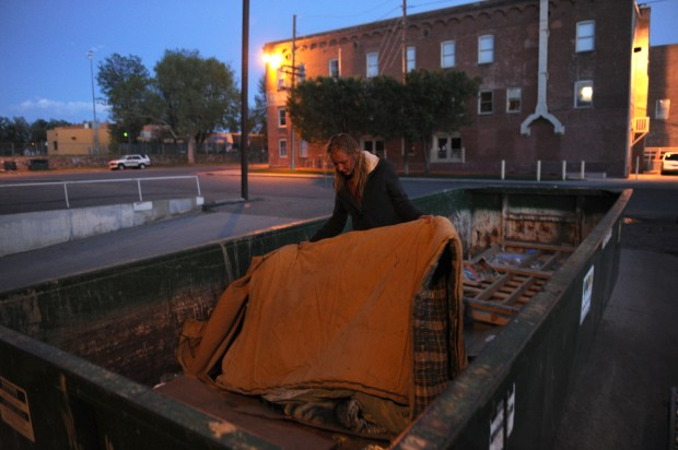 Angel makes her bed in the commercial dumpster she's been living in at 12th and Osage in Denver.