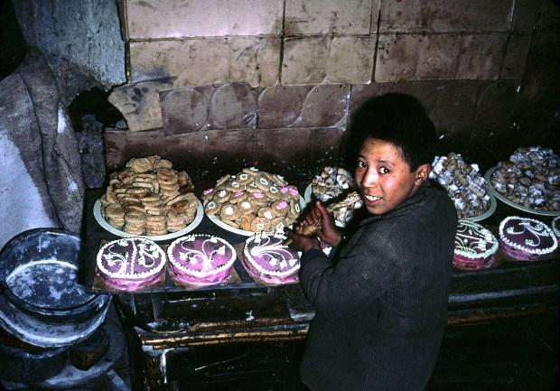 An Afghan boy decorates cakes.