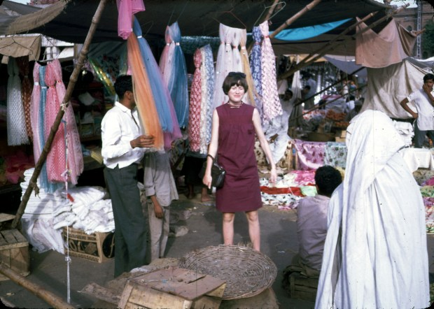 """Jan Podlich on a shopping trip in Istalif. Jan in a short, sleeveless dress and the woman to the right in a chadri (burka).""""We arrived in Kabul one sunshiny morning in June... My dad met us and was able to whisk us through the customs. We proceeded into Kabul in a UN ÒkombiÓ (kind of an old school SUV). I was tired, but I can remember being amazed at the sight of colorful (dark blue, green and maroon) ÒghostsÓ that were wafting along the side of the road. My dad explained there were women underneath those chadris, and that some women had to wear them out in public. We never called the garments Òburkas.Ó Depending on the country, women practicing purdah (Islamic custom requiring women to cover up) wear different styles of coverings, which have different names."""" - Peg Podlich."""