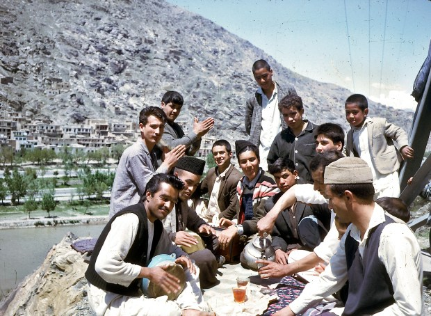 A group of young Afghans share tea and music.
