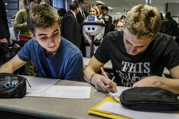 Students work next to a robot designed to allow an absent student to follow the lesson from home on January 21, 2014 in Lyon.