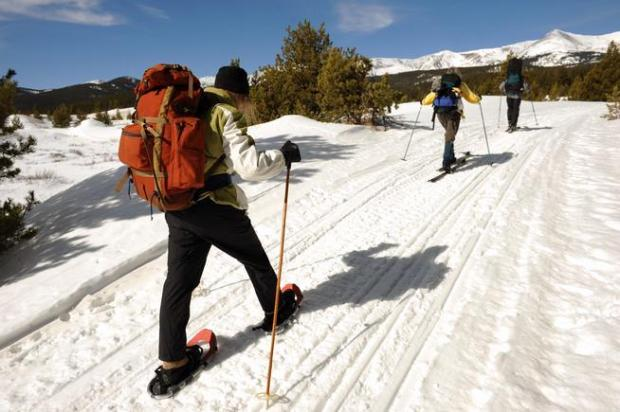 A trio of snowshoers make their way along the trail toward a 10th Mountain Division Hut outside of Leadville .