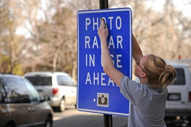 A photo enforcement agent places a photo radar sign on 17th Street in Denver on Feb. 29, 2012.