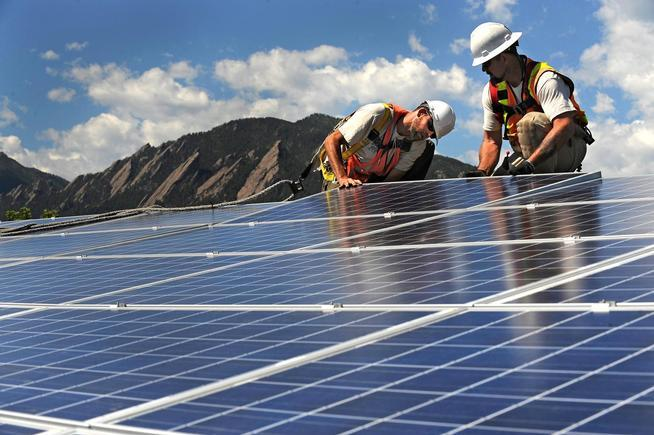Workers with Bella Energy install solar panels on the rooftop of in Boulder on July 25, 2014.