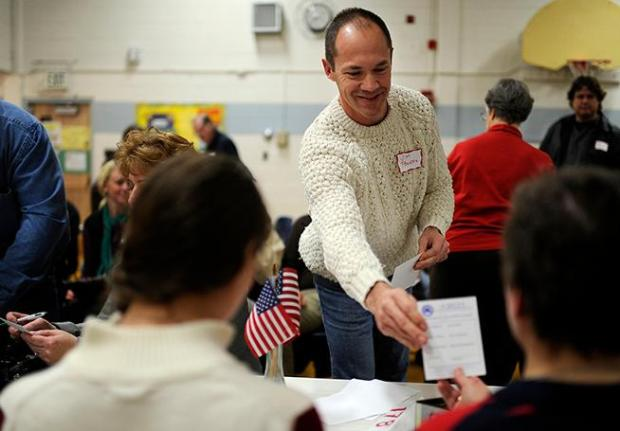 Jim Powers hands the card to vote for Republican caucus at Green Mountain Elementary school gym in Lakewood on Tuesday, Feb. 7, 2012.