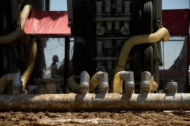 A fracking crew member works inside ...