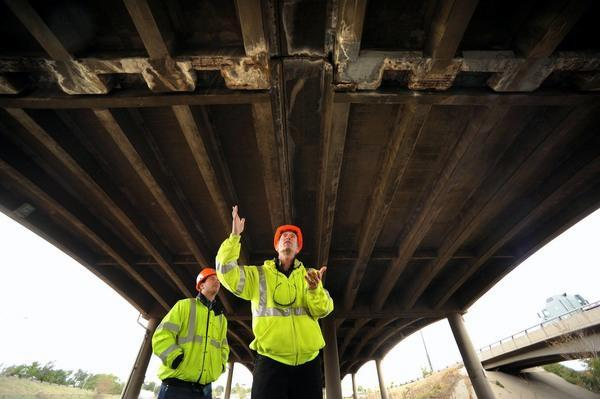 Colorado Department of Transportation engineers Jeff Anderson, right, and Steve Pineiro look at the underside of the Interstate 70 viaduct, where seeping liquids have filtered through expansion joints to eat at concrete piers, girders and columns.
