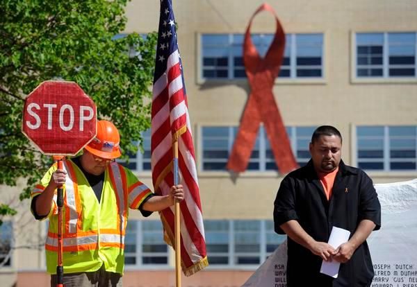 CDOT maintenance worker Richard Gallegos, left, joins Frank Lopez in a moment of silence to honor employees who have died in the line of duty. Lopez's father, Eladio Lopez, was killed in 2004 while working on a section of Interstate 25.