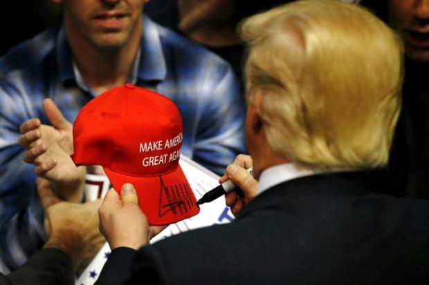 "Republican presidential candidate Donald Trump signs a ""Make American Great Again"" hat for a supporter after speaking at an April 11 campaign rally in Albany, N.Y."