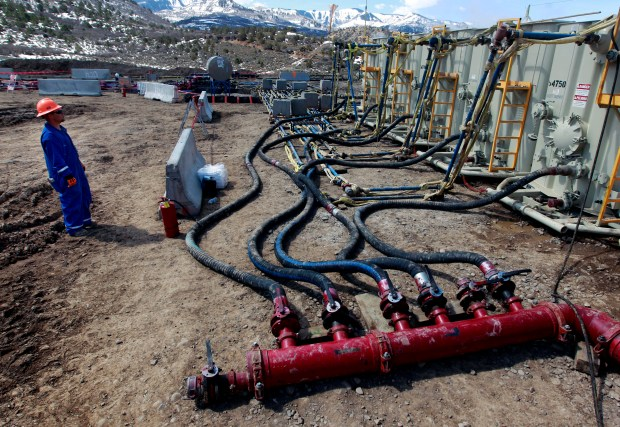 A worker helps monitor water pumping pressure and temperature at a hydraulic fracturing and extraction site on March 29, 2013, outside Rifle in western Colorado.