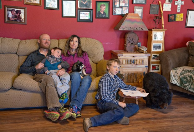 Matt and Cindy Preslar, sit with their sons Max Preslar, right, and Ricky Preslar, who is profoundly physically, and cognitively disabled, at their home.