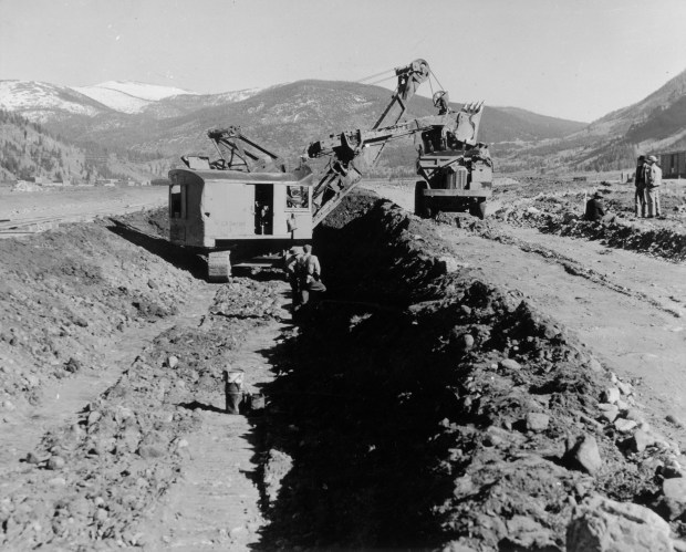 "Construction workers stand in a trench or beside construction equipment near Pando in Camp Hale (Eagle County), Colorado. An excavator, in the re-routed Eagle River bed, reads ""CA Switzer 3."" Men wear overalls and hats. Shows Denver and Rio Grande Western Railroad tracks near the workers and buckets in the trench. (Photo courtesy of Denver Public Library, 10th Mountain Division Collection)"