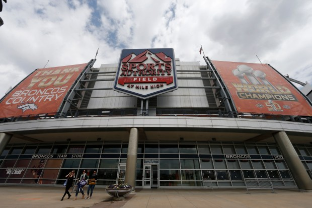 In this Thursday, May 26, 2016, photograph, shoppers leave the team store below the sign for Sports Authority Field at Mile High on the south end of the stadium that is the home of the NFL football team Denver Broncos in Denver.