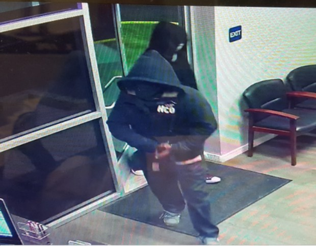 The second person of interest, shown in the back of this photo, was wearing a black hooded sweatshirt, blue jeans and maroon Converse or similar shoes.