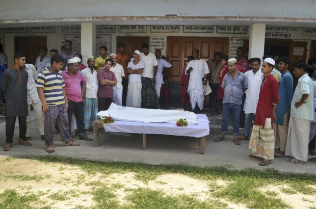 Locals surround the body of a Hindu holy man after assailants hacked him to death in Pabna, 275 kilometres (170 miles) from Dhaka, Friday, June 10, 2016.