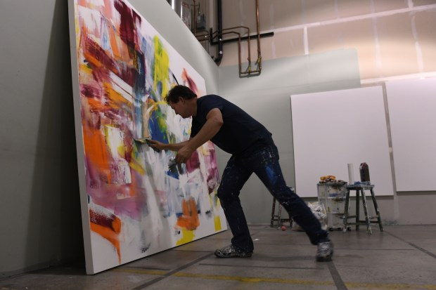 BOULDER, CO - JUNE 13: Artist Will Day continues his work on a large oil on canvas. Businesses at Black Lab Sports, an accelerator in Boulder, spend time in their open spaces at the industrial offices on Monday, June 14, 2016. (Photo by Kathryn Scott Osler/The Denver Post)
