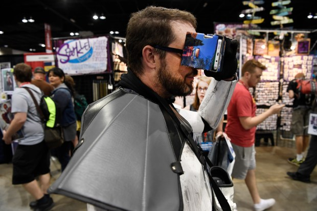 Gary Reynolds looks at a virtual reality comic book through cardboard VR googles designed by students at the Rocky Mountain College of Art and Design at Denver Comic Con at the Colorado Convention Center, Thursday, June 16, 2016.