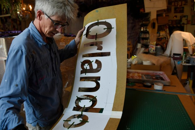 LAKEWOOD, CO - JUNE 16: Artist Lonnie Hanzon holds a stencil of Orlando at his studio in Lakewood while working on a memorial for the Orlando shooting on Thursday, June 16, 2016. It will be on display at the Denver PrideFest this weekend in Civic Center Park. Last year for PrideFest, Hanzon created a giant festive wedding cake. This year's tone is much more somber. (Photo by Cyrus McCrimmon/The Denver Post)