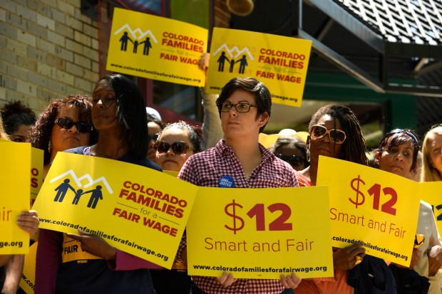 In a file photo, people with the Colorado Families for a Fair Wage campaign hold up signs during their rally on the outdoor patio at Vine Street Pub on May 18 in Denver, Colorado.