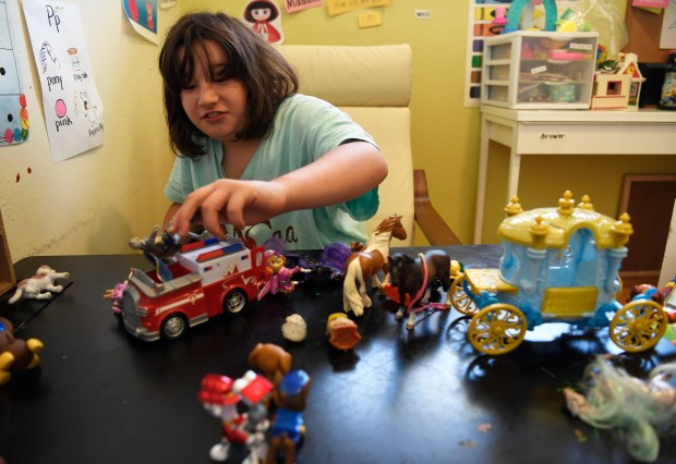 """DENVER, CO - May 12: Madeline Auirre, 10, plays with her favorite toys at her house May 12, 2016. """"Maddie"""" was diagnosed with a rare chromosomal disorder called atypical Rett's syndrome and is cared for 24/7 by family and specialist at home. (Photo by Andy Cross/The Denver Post)"""