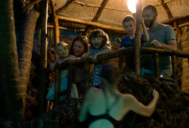 LAKEWOOD, CO - JUNE 24: The Whitney family from Denver watches as diver Caitlin Torgerson, 19, climbs a cliff near their table. From left to right are Lillian, 4, mom Rochelle, Ellora, 7, Marshall 6, and dad Nick. The popular cliff divers at Casa Bonita in Lakewood entertain their lunch crowd on Friday, June 24, 2016, (Photo by Kathryn Scott Osler/The Denver Post)
