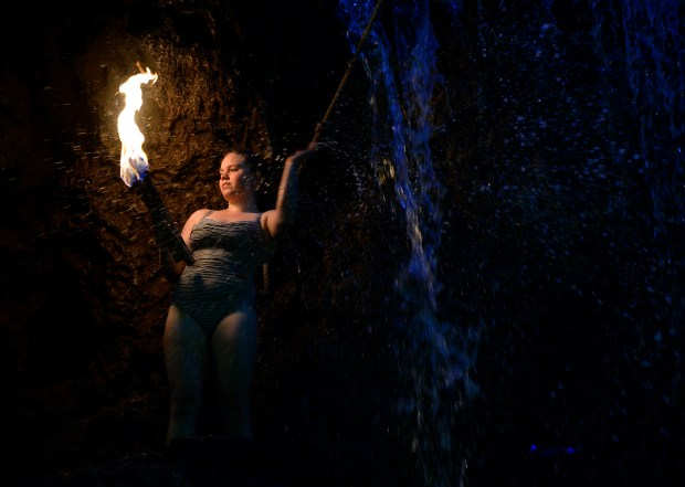 LAKEWOOD, CO - JUNE 24: Georgia Pullis, 20, prepares three torches for juggling and then dives in to the pool holding them in her hands. The popular cliff divers at Casa Bonita in Lakewood entertain their lunch crowd on Friday, June 24, 2016, (Photo by Kathryn Scott Osler/The Denver Post)