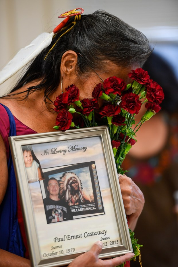 DENVER, CO - JUNE 08: Lynn Eagle Feather weeps as she buries her face in a bouquet of carnations while holding a sign in memory for her son Paul Ernest Castaway who was shot by DPD in 2015. Lynn Eagle Feather attended the Colorado Latino Forum discussion June 8, 2016 at Escuela Tlatelolco to discuss the impact of police shootings in the Latino community. The police chief and safety director will share the stage with two mothers who have lost their sons in police shootings. (Photo By John Leyba/The Denver Post)
