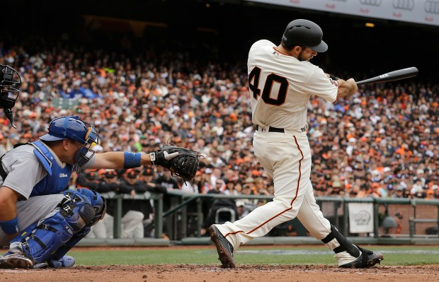 FILE - In this April 9, 2016, file photo, San Francisco Giants' Madison Bumgarner (40) hits a solo home run in front of Los Angeles Dodgers catcher A.J. Ellis during the second inning of a baseball game in San Francisco. San Francisco manager Bruce Bochy said he plans to use his slugging pitcher Bumgarner instead of a designated hitter Thursday, June 30, 2016, night when the Giants visit the Oakland Athletics. (AP Photo/Jeff Chiu, File)