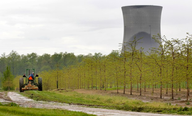 A worker is seen in the area surrounding a tree farm in North Perry, Ohio, near the two cooling towers of the Perry Nuclear Power Plant looming in the background, May 2011. The risk of an earthquake causing a severe accident at a nuclear power plant is up to 24 times greater than previously believed, according to an AP analysis of preliminary government data, and the nation's nuclear regulator believes that a quarter of reactors may need modifications to make them safer.