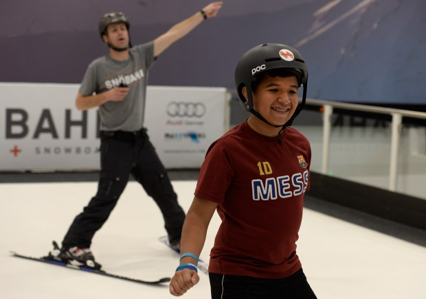 CENTENNIAL, CO - JUNE 20: This is the first time Joshua Herrera, 11, has ever strapped on a pair of skis and breaks out into a big smile as he begins his lessons with ski instructor Branden Burden, left. Instructors work with students at the new Snobahn Indoor Ski and Snowboard center in Centennial on Monday, June 20, 2016. The facility, located on the Streets at SouthGlenn shopping center, will host it's grand opening on Friday, June 24, 2016. (Photo by Kathryn Scott Osler/The Denver Post)