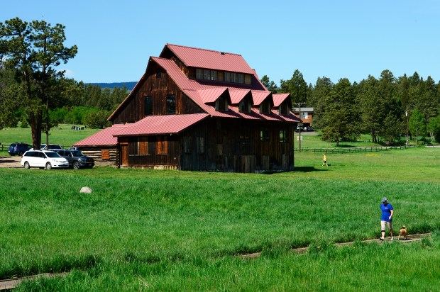 EVERGREEN, CO - JUNE 8: A hiker walks a trail that runs alongside the barn at Alderfer/Three Sisters Park on June 8, 2016, in Evergreen, Colorado. Evergreen Park & Recreation District is looking to expand programming the historic barn at Alderfer/Three Sisters Park. Built in the early 1900s, the barn already plays host to activities such as yoga, youth running, hikes, and more. (Photo by Anya Semenoff/The Denver Post)