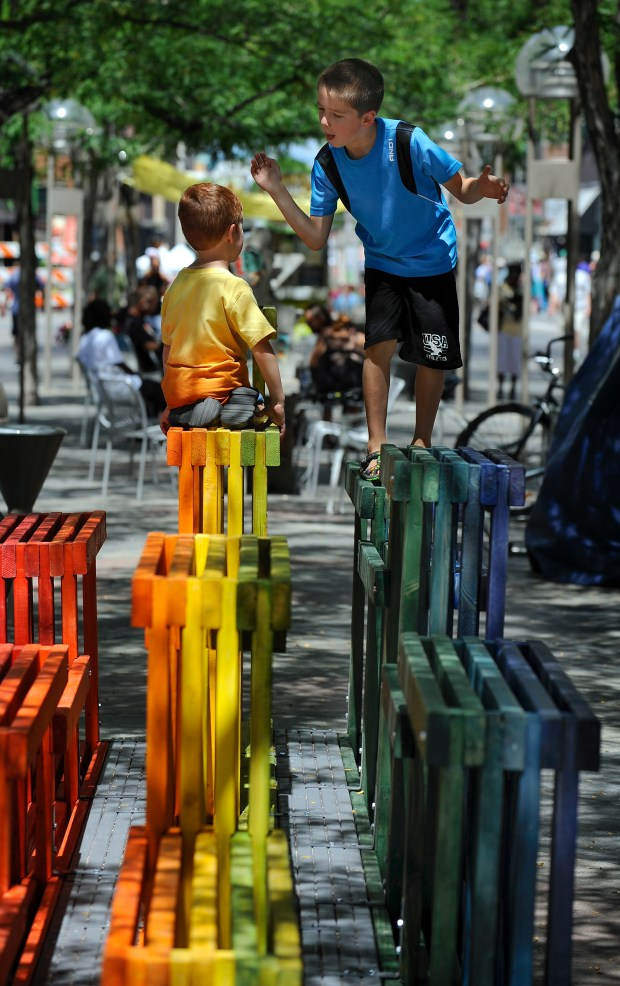 Sean Cason, 7, right, and brother Jacob, 4, visiting from Dawsonville , GA, perch themselves atop the Rainbow Street Seating prototype by Nick Fish, Yong Huang, and Tony Yue, the AtelierHay and WorthGroup. The Prototyping Festival takes place in downtown Denver along the 16th Street Mall on Saturday, July 23, 2016.