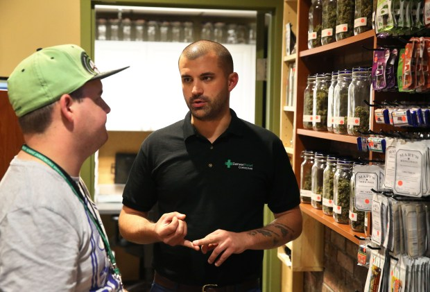 In this Aug. 25, 2014 photo, marijuana store Denver Relief co-owner Kayvan Khalatbari, right, talks with his employee Jeff Botkin his medical and recreational marijuana shop in Denver. Khalatbari also runs Denver Relief Consulting, which assists current and would-be marijuana-related businesses around the country, as well as owning a chain of pizza restaurants in Denver. (AP Photo/Brennan Linsley)