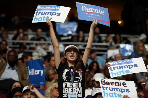 An attendee holds signs in support of Sen. Bernie Sanders on the first day of the Democratic National Convention at the Wells Fargo Center Philadelphia on Monday.