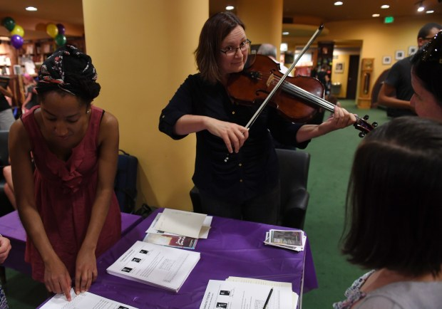 Catherine Beeson of the Colorado Symphony plays her viola as a way to teach children how to spell out their names using musical notes at the Tattered Cover Book Store at 2526 E. Colfax Ave. in Denver.