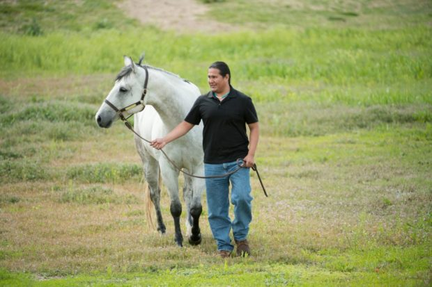 "Patrick Succo, a second-year DVM student at Colorado State University, with ""Blue,"" a horse at CSU's Equine Center. Succo helped to launch a veterinary outreach program to teach animal care and medical skills to high school students, livestock producers and pet owners in the Navajo Nation."