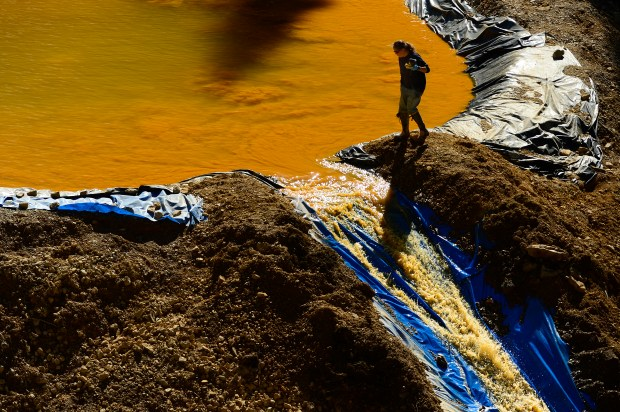 SAN JUAN COUNTY, CO - AUGUST 13: A woman from Weston Solutions walks next to one of the retention ponds at the bottom of Gold King Mine on August 13, 2015 at Gladstone townsite. Members of the EPA, Environmental Restoration, Weston Solutions and the U.S. Coast Guard are working on cleaning up the water in the four retention ponds and helping with the creation of the fifth. (Photo By Brent Lewis/The Denver Post)